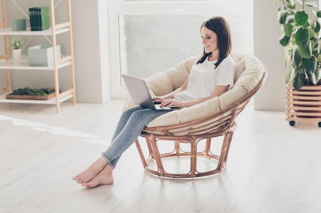 Pełnowymiarowe zdjęcie młodej damy siedzącej na wiklinowym krześle, pracującej na laptopie, noszącej białą dżinsową koszulkę w domu w domu