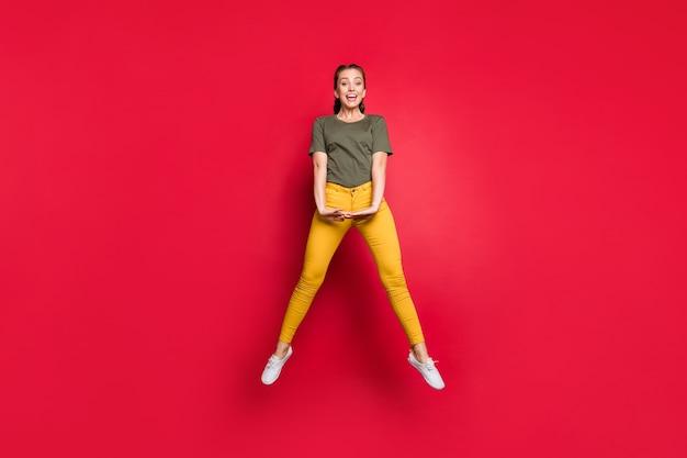 Pełnowymiarowe zdjęcie podekscytowanej tysiącletniej pani skaczącej wysoko spędzającej wolny czas wesoły nastrój radosny ubranie na co dzień żółte spodnie zielona koszulka na białym tle czerwony kolor tło