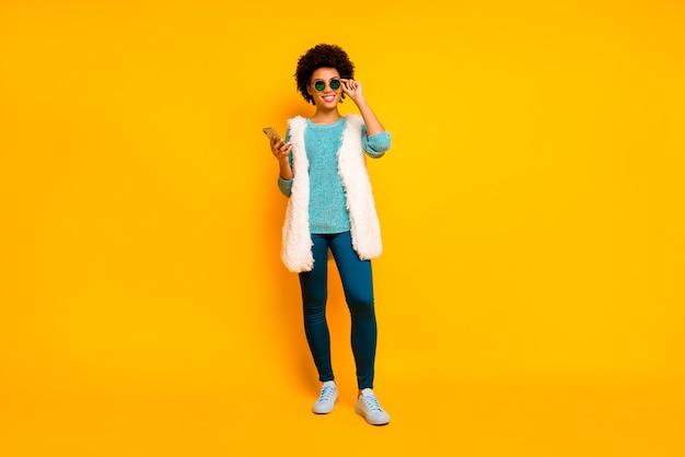 Pełnowymiarowe zdjęcie pozytywne afroamerykanka spacer relaksować się używać smartfona podążaj za komentarzem aktualności nosić niebieskie spodnie spodnie turkusowy sweter stylowy trenyd biały izolowany żółty kolor ściana