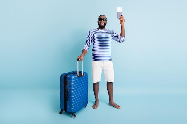 Pełnowymiarowe zdjęcie pozytywne śmieszne afroamerykański mężczyzna posiadający dokumenty turystyczne mają wózki ciesz się wypoczynkiem weekendowym nosić okulary przeciwsłoneczne kamizelka w paski białe szorty na białym tle niebieski kolor ściana