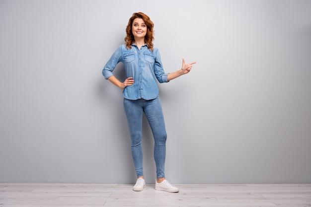 Pełnowymiarowe zdjęcie pozytywne wesoła kobieta biznesu promotor punkt palec wskazujący copyspace obecne reklamy sugerują wybierz promocję nosić dobry wygląd ubrania obuwie izolowany szary kolor ściana