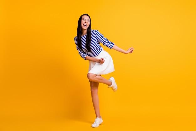 Pełnowymiarowe zdjęcie pozytywnej, wesołej, podekscytowanej, energicznej dziewczyny tańczącej, cieszącej się letnim weekendem w dyskotece, noszącej dobry strój na białym tle na jasnym kolorowym tle
