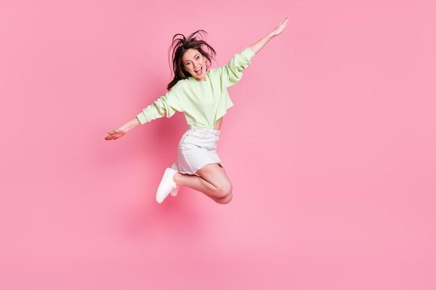 Pełnowymiarowe zdjęcie profilowe atrakcyjnej śmiesznej damy skaczącej wysoko rozłożone ramiona jak skrzydła latające nosić casual crop sweter nagi brzuch spódnica buty na białym tle różowy pastelowy kolor tła