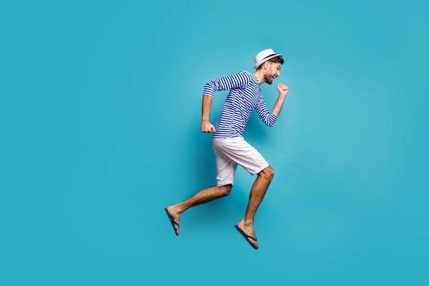 Pełnowymiarowe zdjęcie profilowe funky turysta skaczący wysoko w pośpiechu niskie ceny odzież na zakupy w paski marynarska koszula kamizelka czapka spodenki japonki na białym tle niebieski kolor