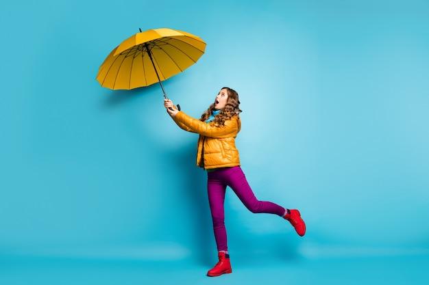 Pełnowymiarowe zdjęcie profilowe ładnej podróżniczki trzymającej jasny parasol latający w górę z wiejącym wiatrem nosić żółty płaszcz szalik fioletowe spodnie czerwone obuwie izolowany niebieski kolor ściana