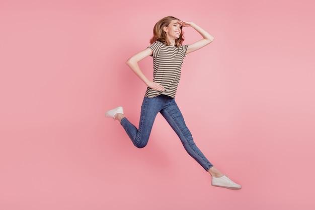 Pełnowymiarowe zdjęcie profilowe młodej kobiety szczęśliwego pozytywnego uśmiechu czekamy na skok na białym tle nad różowym kolorem tła