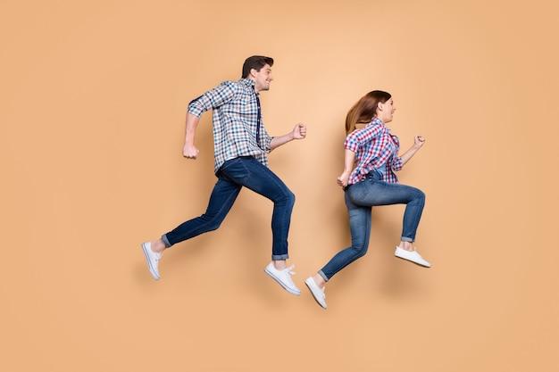 Pełnowymiarowe zdjęcie profilowe po stronie rozmiaru ciała wesołej pozytywnej dziecięcej uroczej słodkiej ładnej pary w dżinsach obuwie dżinsowe koszula w kratkę na białym tle na beżowym pastelowym tle