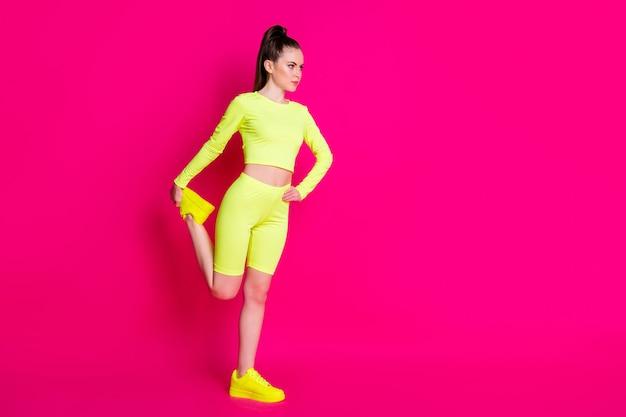 Pełnowymiarowe zdjęcie profilowe poważnej sportowej dziewczyny rozciągającej nogę wygląda na pustą przestrzeń na białym tle nad różowym połyskiem koloru tła