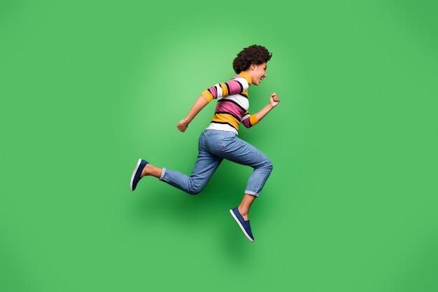 Pełnowymiarowe zdjęcie profilowe przedstawiające funky afro-amerykańską dziewczynę, która biegnie po niesamowitych zniżkach w czarny piątek, nosząc stylowe ubrania