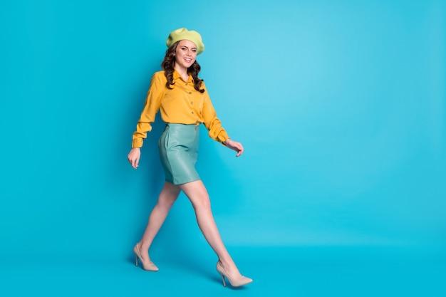Pełnowymiarowe zdjęcie profilowe słodkiej atrakcyjnej damy cieszyć się odpoczynkiem zrelaksować się iść spacer copyspace nosić dobry wygląd ubrania nakrycia głowy buty na białym tle nad niebieskim kolorem tła
