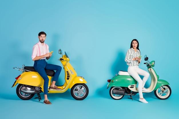 Pełnowymiarowe zdjęcie profilowe śmiesznej pani facet z otwartymi ustami prowadzącej dwa rocznika związek motoroweru trzymaj telefony czytaj sprzedaż reklama odzież wizytowa ubrania izolowane niebieski kolor ściana