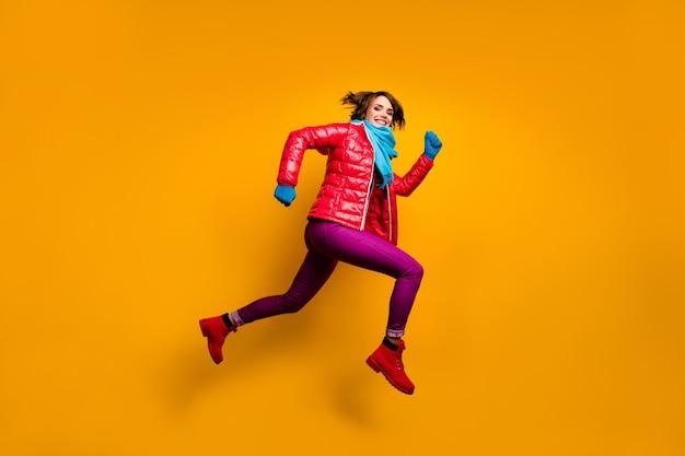 Pełnowymiarowe zdjęcie profilowe śmiesznej pani podskakującej w pośpiechu wyprzedaży na zakupy ubranie na co dzień czerwony płaszcz niebieski szalik rękawiczki spodnie obuwie