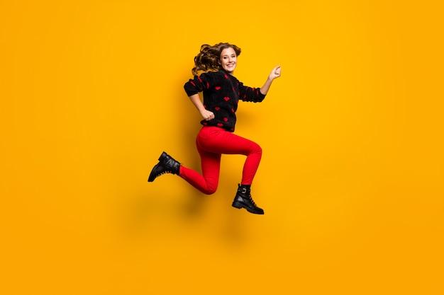 Pełnowymiarowe zdjęcie profilowe śmiesznej pani podskakuje z dużą prędkością pędząc niskie ceny uzależniony kupujący nosić sweter w serduszka czerwone spodnie obuwie