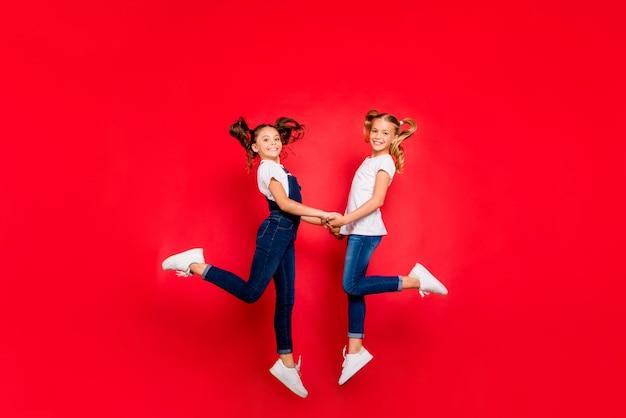 Pełnowymiarowe zdjęcie profilowe z boku dwóch małych dzieci, które mają weekendy świąteczne, trzymaj się skoku, trzymaj się za ręce, nosić białą koszulkę dżinsowe dżinsy kombinezony trampki izolowane na błyszczącym kolorze tła