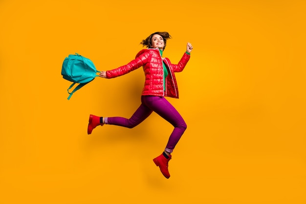 Pełnowymiarowe zdjęcie profilowe z boku wesołej, funky młodzieżowej dziewczyny jump run dzień pracy w college'u trzymaj niebieski plecak nosić fioletowy połysk stylowe modne ubrania czerwone buty