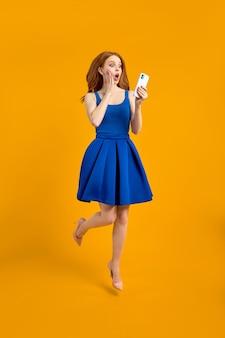 Pełnowymiarowe zdjęcie profilowe zaskoczonej rudej kobiety w sukience skoku skorzystaj z wyszukiwarki smartfonów rabaty ru...