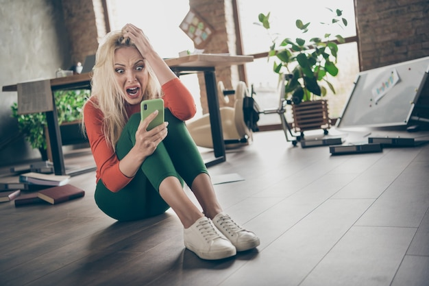 Pełnowymiarowe zdjęcie przytłoczonej, szalonej, szalonej kobiety, przedstawicielka start-upu, agent siedzieć na podłodze, korzystać ze smartfona, otrzymywać powiadomienie o zwolnieniu, krzyczeć panika dotyk blond włosy w brudnym biurze na poddaszu w miejscu pracy