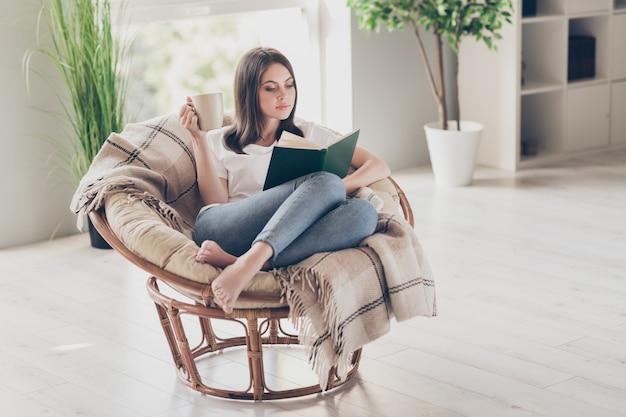 Pełnowymiarowe zdjęcie skoncentrowanej dziewczyny czytającej książkę siedzącą na wiklinowym krześle z filiżanką kawy w białej koszulce w domu w domu