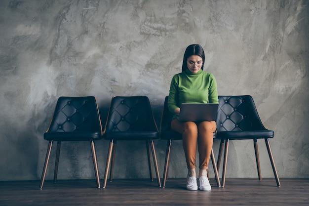 Pełnowymiarowe zdjęcie skupionej kobiety używającej laptopa i umysłu do stworzenia projektu z godziną przed egzaminem pozostającym odizolowanym w pobliżu pustej przestrzeni szary kolor ściany betonowe tło