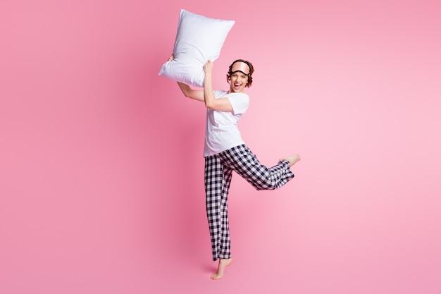 Pełnowymiarowe zdjęcie śmiesznej pani podnosi poduszkę i przygotowuje się do walki na różowej ścianie