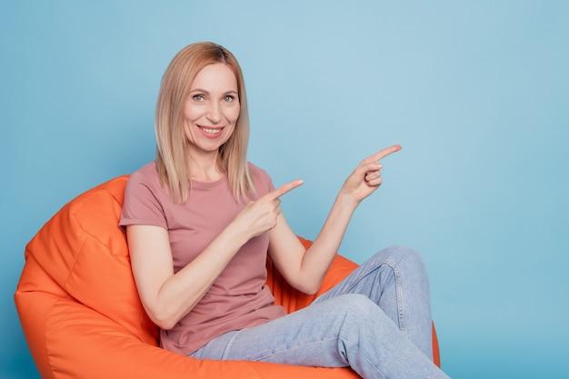 Pełnowymiarowe zdjęcie szczęśliwej kobiety wskazuje palce puste miejsce siedzieć na krześle fasoli nosić reklamę koszulki na białym tle na niebieskim tle