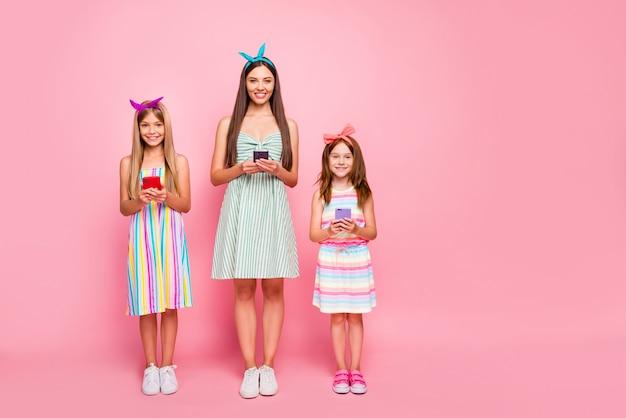 Pełnowymiarowe zdjęcie uroczej kobiety i dwóch dzieci w wieku szkolnym mających blond fryzurę brunetki użyj urządzenia nosić opaski na głowę spódnicy na białym tle na różowym tle