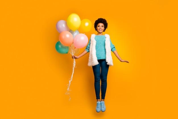 Pełnowymiarowe zdjęcie wesołej afroamerykanki balony z wyskokiem, którą dostaje na rocznicę nosić puszyste stylowe modne kamizelki turkusowy sweter niebieskie jasne buty izolowane połysk kolor ściana