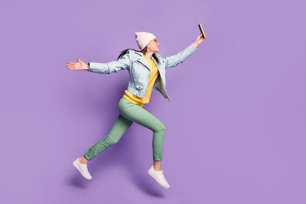 Pełnowymiarowe zdjęcie wesołej dziewczyny skakać mieć wolny czas zrobić selfie martphone nosić skórzaną kurtkę zielone spodnie spodnie nakrycia głowy okulary przeciwsłoneczne na białym tle fioletowy kolor tła