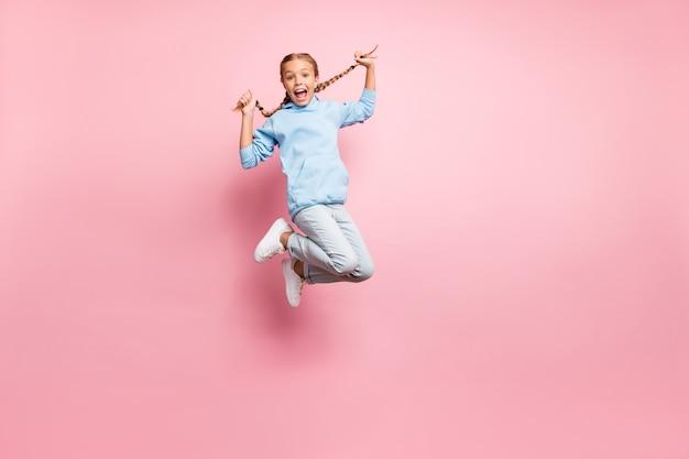 Pełnowymiarowe zdjęcie wesołej, pozytywnej ekstazy, uszczęśliwionej radosnej dziewczyny, podskakującej w dżinsach, dżinsowej niebieskiej bluzie, swetrze izolowanym na pastelowym tle