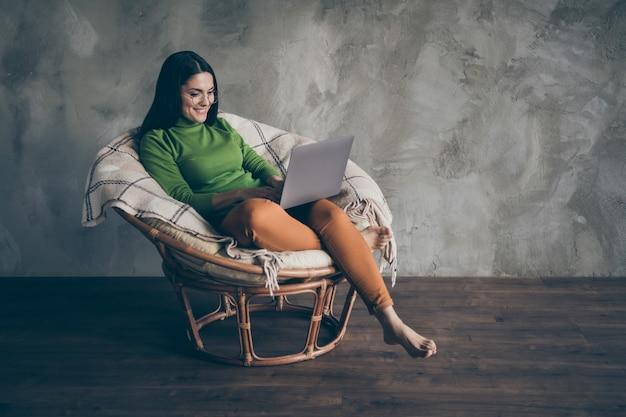 Pełnowymiarowe zdjęcie wesołej ślicznej ładnej ładnej bosej kobiety w pomarańczowych spodniach pracującej nad prezentacją projektu za pomocą laptopa izolowany szary kolor ściany betonowe tło