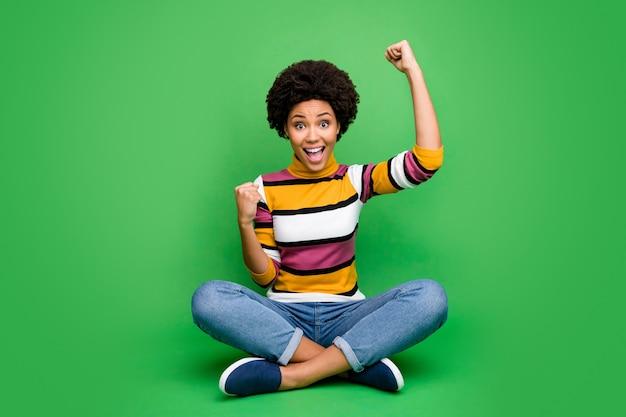 Pełnowymiarowe zdjęcie wesołej, zachwyconej, szczęśliwej afroamerykanki siedzącej ze skrzyżowanymi nogami złożonymi wygranej na loterii wznieść pięści krzyczeć tak nosić dobry wygląd strój