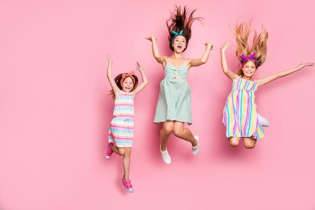 Pełnowymiarowe zdjęcie wesołych pań skaczących z krzykiem w spódnicy sukienki na białym tle na różowym tle
