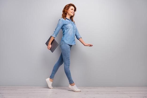 Pełnowymiarowe zdjęcie z boku profilu urocza inteligentna niezależna dyrektor generalny kobieta idź na spacer spotkanie biznesowe trzymaj netbook laptop nosić dobry wygląd nowoczesny strój gumowe buty izolowane szary kolor ściana