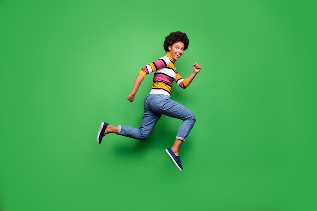 Pełnowymiarowe zdjęcie z profilu po stronie pozytywnej wesołej afroamerykanki skaczącej po jesieni czarny piątek okazja nosić dżinsowy strój