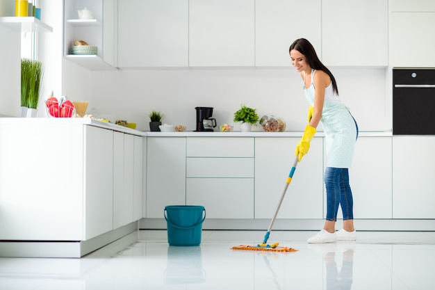 Pełnowymiarowe zdjęcie z profilu pozytywnej, wesołej dziewczyny, która myje podłogę mopem w białej podkoszulce żółte gumowe rękawiczki w kropkowany fartuch spadła zadowolona z prac domowych w kuchni w domu