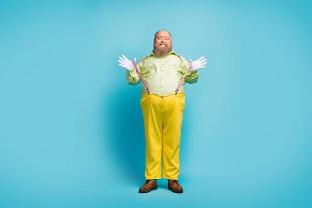 Pełnowymiarowe zdjęcie zabawnego mężczyzny ciągnącego szelki na niebieskim tle