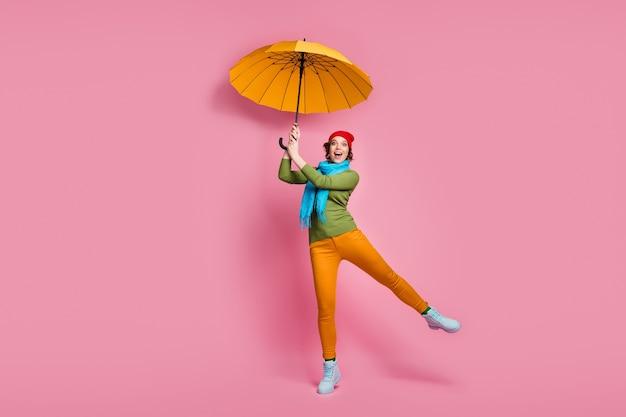 Pełnowymiarowe zdjęcie zaskoczonej dziewczyny złapać jej połysk parasol krzyczeć wow omg nosić niebieskie czerwone nakrycia głowy spodnie zimowe buty sweter izolowany na różowej ścianie