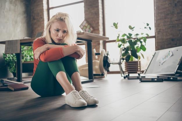 Pełnowymiarowe zdjęcie zdenerwowanej kobiety dyrektor generalny zwolniony siedzieć na podłodze czuć się samotny samotność mieć problemy z uruchomieniem firmy w brudnym biurze w miejscu pracy na strychu w czerwonych zielonych spodniach z golfem