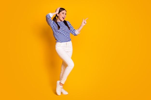 Pełnowymiarowe zdjęcie zdziwiona pod wrażeniem dziewczyna punkt palec wskazujący copyspace zademonstrować niesamowitą reklamę promocja krzyczeć wow omg nosić dobry wygląd ubrania na białym tle jasny połysk kolor tła