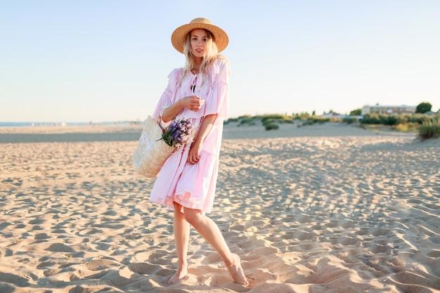 Pełnowymiarowy obraz blond dziewczyny w ślicznej różowej sukience tańczącej i mającej fu na plaży. trzyma słomkową torbę i kwiaty