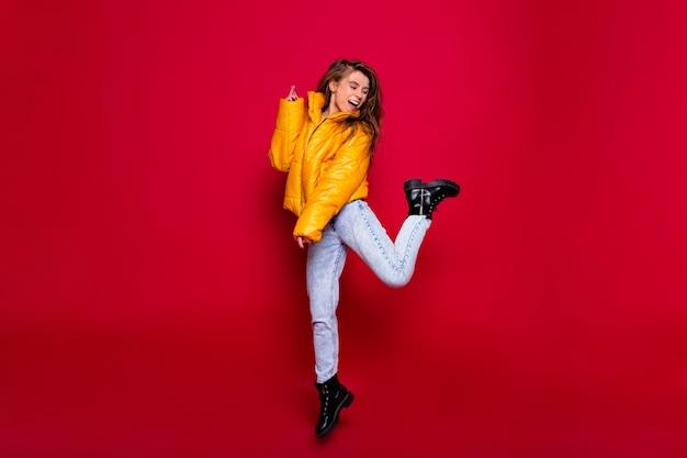 Pełnowymiarowy portret aktywnej, szczęśliwej dziewczyny z długimi włosami ubrana w żółtą kurtkę i dżinsy ze szczęśliwym uśmiechem na czerwonej ścianie. portret sfrustrowanej młodej kobiety w sukni na białym tle na czerwonym tle