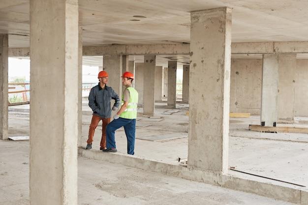 Pełnowymiarowy portret dwóch pracowników omawiających inżynierię w przestrzeni kopii na placu budowy