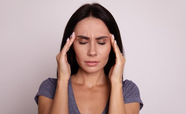 Pełnowymiarowy portret dziewczyny, która stoi twarzą do aparatu z zamkniętymi oczami i dotyka palcami skroni jako oznaka stresu lub bólu głowy