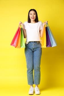 Pełnowymiarowy portret pięknej azjatki idącej na zakupy, trzymającej papierowe torby ze sklepów i uśmiechniętej, stojącej w dżinsach i białej koszulce na żółtym tle.