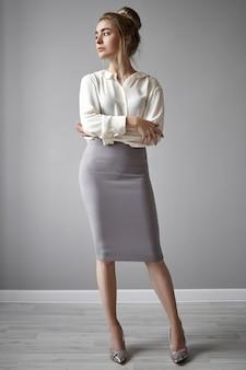 Pełnowymiarowy portret pięknej, pewnej siebie, odnoszącej sukcesy, młodej szefowej w stylowych butach na wysokim obcasie, spódnicy midi i białej formalnej koszuli odwracającej wzrok i trzymającej ręce skrzyżowane na piersi