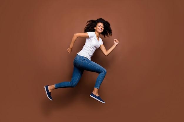 Pełnowymiarowy portret profilu śmiesznej ciemnoskórej pani skaczącej w zawodach sportów wysokich uczestnik pędzący na mecie nosić białą koszulkę dżinsową.