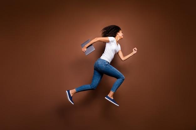 Pełnowymiarowy portret profilu śmiesznej ciemnoskórej pani skaczącej wysoko trzymającej notatnik pośpiesznie wejdź do klasy nosić casualową białą koszulkę dżinsową.