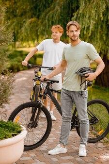 Pełnowymiarowy portret przystojnego brodatego rowerzysty z kaskiem w dłoni i jego przyjaciela stojącego na zewnątrz