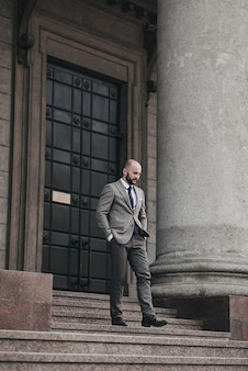 Pełnowymiarowy portret przystojnego mężczyzny w pełnym garniturze i butach schodzącego po schodach