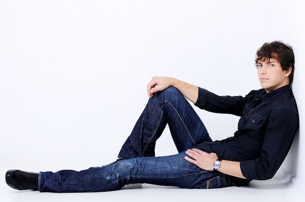 Pełnowymiarowy portret przystojnego seksownego mężczyzny leżącego i pozującego w studio